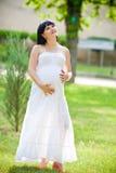 Беременная женщина ослабляя в парке Стоковое фото RF