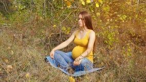 Беременная женщина ослабляет с закрытыми глазами в положении лотоса сток-видео
