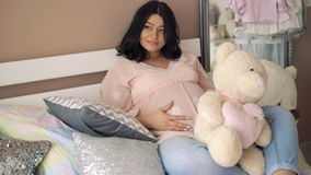 Беременная женщина отдыхая на кровати с плюшевым медвежонком и штрихуя живот 4K видеоматериал