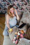 Беременная женщина отдыхая на софе и говоря на телефоне Стоковое фото RF