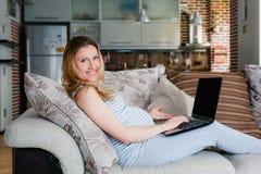 Беременная женщина отдыхая на софе и работая на компьтер-книжке Стоковое Изображение RF