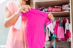 Беременная женщина перед шкафом в комнате childs Стоковая Фотография