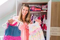 Беременная женщина перед шкафом в комнате childs Стоковые Фото