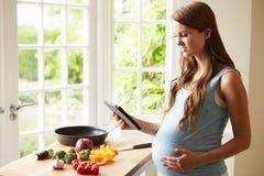 Беременная женщина после рецепта на таблетке цифров стоковое фото rf