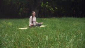 Беременная женщина практикует йогу в парке сидя на половике, сидящ в положении лотоса и размышляет сток-видео