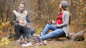 Беременная женщина при ее супруг отдыхая огнем видеоматериал