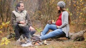 Беременная женщина при ее супруг отдыхая огнем акции видеоматериалы