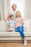 Беременная женщина при дочь сидя на софе и усмехаясь человеке стоя позади Стоковое фото RF