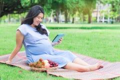 Беременная женщина при таблетка ослабляя в саде Стоковые Изображения RF