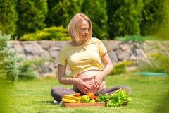 Беременная женщина сидит на траве перед подносом плодоовощ и портретирует сердце с ее руками на ее животе Стоковое Изображение