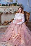 Беременная женщина сидя в красивом платье на кресле Концепция материнства стоковые фотографии rf