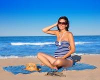 Беременная женщина сидя на голубом песке пляжа Стоковые Изображения RF