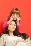 Беременная женщина сидя на софе с дочерью Стоковая Фотография RF