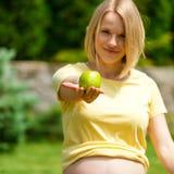 Беременная женщина сидя на траве и держа вне яблоко в руке Стоковое Фото