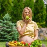 Беременная женщина сидя на траве и держа яблоко в руке Стоковое Изображение RF