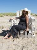 Беременная женщина сидя на деревянном стуле на beac стоковые изображения