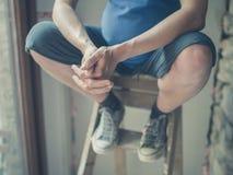 Беременная женщина сидя на лестнице шага Стоковые Изображения RF