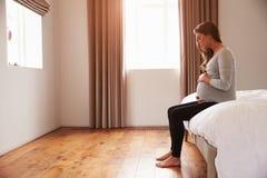 Беременная женщина сидя на кровати держа живот Стоковое Изображение RF