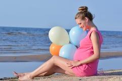 Беременная женщина сидя на пляже Стоковые Изображения RF