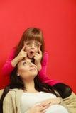 Беременная женщина сидя на софе с дочерью Стоковое Изображение RF