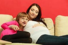 Беременная женщина сидя на софе с дочерью Стоковая Фотография