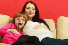 Беременная женщина сидя на софе с дочерью Стоковое Фото