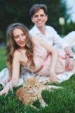Беременная женщина сидя на траве и штрихуя ее живот Стоковые Изображения