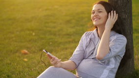 Беременная женщина слушая к музыке на природе сток-видео