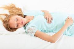 Беременная женщина спать на белом листе стоковые изображения rf