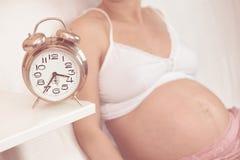 Беременная женщина с будильником Стоковые Изображения