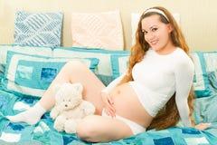 Беременная женщина с длинним плюшевым медвежонком волос и игрушки стоковые изображения