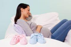 Беременная женщина с добычами младенца на таблице Стоковые Изображения