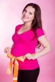Беременная женщина с оранжевой лентой на ее животе Стоковые Фотографии RF
