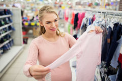 Беременная женщина с одеждами младенца на магазине одежды Стоковая Фотография RF