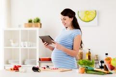Беременная женщина с ПК таблетки варя дома Стоковое Изображение RF