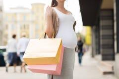 Беременная женщина с хозяйственными сумками на улице города Стоковое Фото