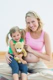Беременная женщина усмехаясь на камере с ее молодой дочерью Стоковые Фото