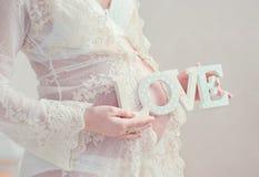 Беременная женщина любяще обнимает живот Стоковое Изображение RF