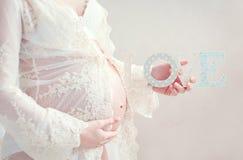 Беременная женщина любяще обнимает живот Стоковые Изображения RF