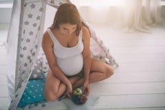 Беременная женщина Ealthy есть плодоовощ в комнате ` s детей в комнате ` s детей стоковое изображение rf