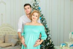 Беременная кавказская женщина нося голубое платье стоя с супругом около рождественской елки стоковое фото