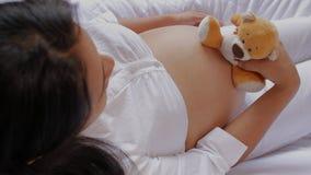 Беременная латино-американская женщина сидя в плюшевом мишке кресла держа и двигая близко к ее животу акции видеоматериалы