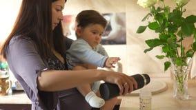 Беременная мать варя с ее сыном младенца в кухне и имея потеху - синь азиатского смешанного мальчика ребенка этничности нося акции видеоматериалы