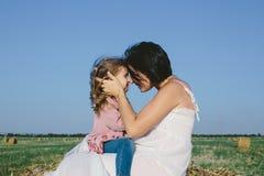 Беременная мать в белом платье обнимая ее дочь внешнюю Стоковые Фотографии RF