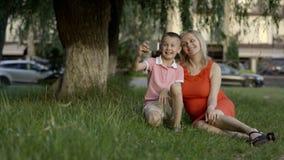 Беременная мать делает sephi с ее самым старым сыном на береге озера Они радостно усмехаются на камере В файле сток-видео