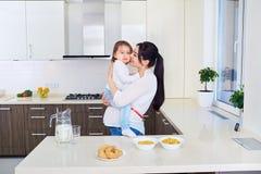 Беременная мать играя с дочерью малыша на кухне Стоковое фото RF
