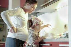 Беременная мать и ее дочь варя в кухне стоковые фото