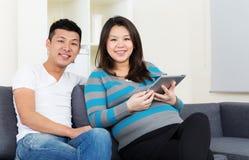 Беременная мать и отец используя цифровую таблетку стоковое изображение rf