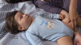 Беременная мать кладя с ее сыном младенца на кровать спальни играя и имея потеху - азиатский смешанный мальчика ребенка этничност сток-видео