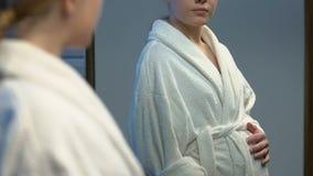 Беременная молодая женщина в купальном халате смотря tummy в зеркале, ожидании младенца акции видеоматериалы